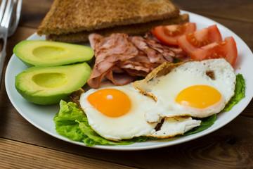 Healthy breakfast. Avocado, eggs sandwich with whole grain bread on wooden background. Copy space
