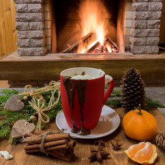Cozy scene before fireplace with mug of hot chocolate,tangerine fruit, cinnamon sticks.