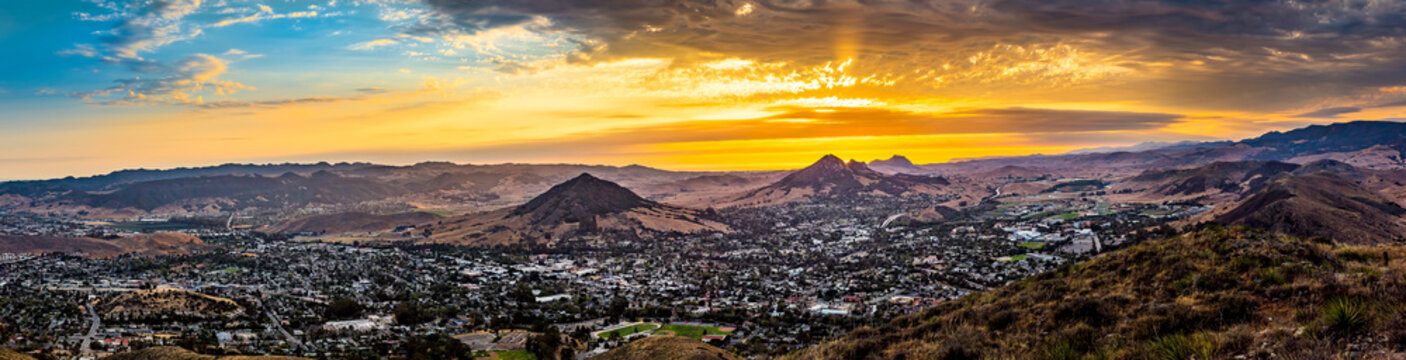 Panoramic Yellow Sunset Over City and Peaks