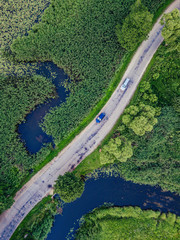 Aerial Photo of Car Driving on the Road going by the River under the Trees, Top Down View in Early Spring on Sunny Day