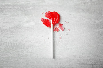 Broken heart shaped lollipop on gray background, top view. Relationship problems