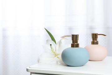 Stylish soap dispensers and lily on table against blurred background. Space for text