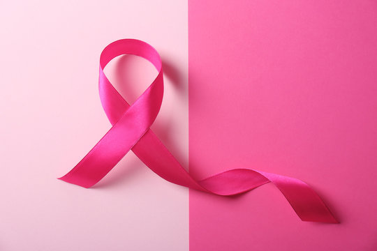 Pink ribbon and space for text on color background. Breast cancer awareness concept