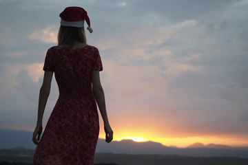 beautiful girl in a red dress and Christmas hat standing looks at the beautiful sunset. back view.