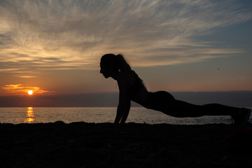 young woman does exercise at sunrise