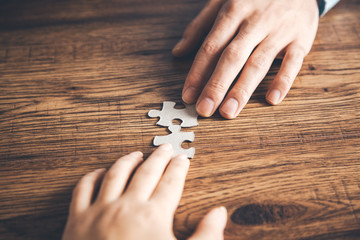 team hands holding puzzle on desk