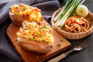 Baked potatoes with bacon, mushrooms and green onions in a rustic style on a wooden board. Close-up