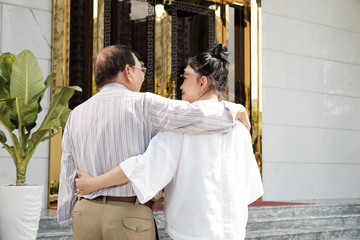 Hugging happy senior Vietnamese couple coming to hotel for summer vacation