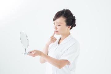 白衣を着て鏡で自分を見る女性