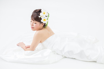 白いドレスを着た髪飾りつけた横になる女性