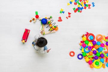 Kid plays among toys.