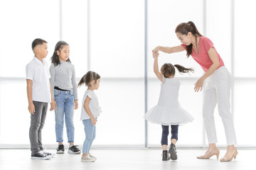 Asian woman in pink shirt dance with little Asian girl, Asian boy and gilrs look at them, they stand in front of big white window.