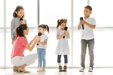 Teacher teaching group of kids to sing.