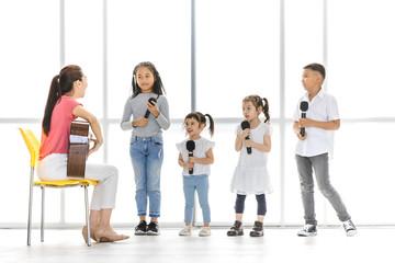 Asian teacher is teaching children to sing.