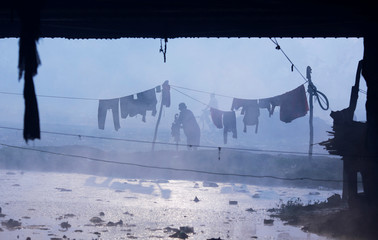 A man washes clothes at a handpump under a bridge over the Yamuna river on a foggy winter morning in New Delhi