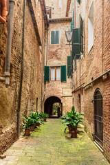 Medieval narrow street Vicolo degli Orefici in Siena, Tuscany, Italy.