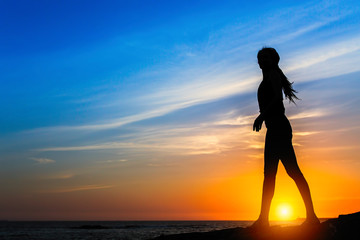 Silhouette of slim woman on the sea coast during amazing sunset.