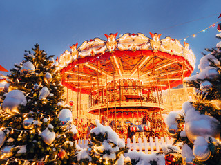 Carousel on Red Square decorated and arranged for Christmas New Year. Christmas fair. Fabulous Luminous roundabout from dream of childhood