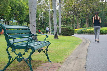 Outdoor green wooden chair at park with green nature.