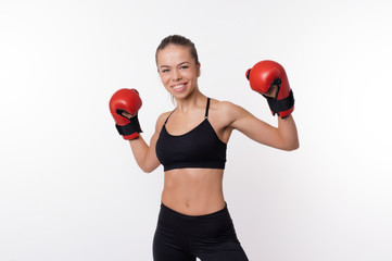 Cheerful fitness woman posing with boxing gloves over white background