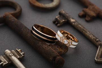 Pair of wedding enamel rings on gray background with vintage rusty keys