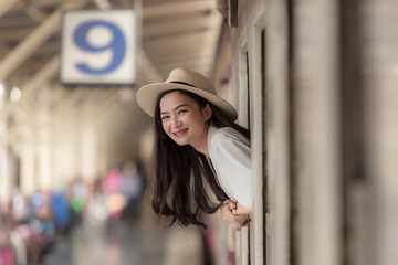 A beautiful charming young asian girl in panama hat move out from train windows with smiling on her face at platform station. Feeling look happy and enjoy on the train. Portrait lady on travel concept