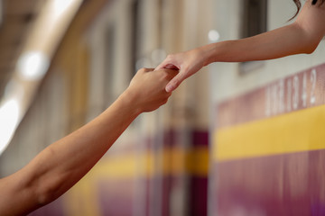 Couple lover touching hand each other in train station. Non verbal communication.