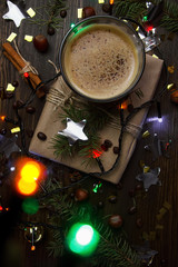 Gift wrapped in craft paper on wooden background. A cup of coffee with froth. Decor of coffee beans, confetti, garland, fir branches