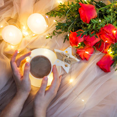 Composition: red roses with boxwood, garlands, candles, star and cup coffee (tea) in hand