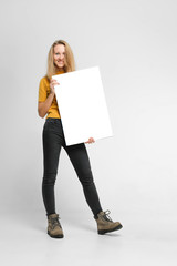 Positive laughing woman wearing black jeans and yellow t-shirt with blondie hair, toothy smile is holding white big mockup poster isolated on white background