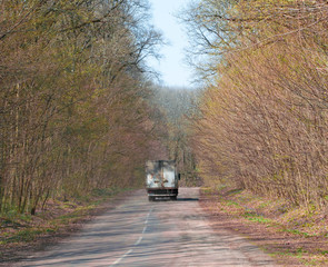 The road to the forest. A truck is driving along a forest road.