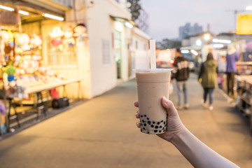 A young woman is holding a plastic cup of bubble milk tea with a straw at a night market in Taiwan, Taiwan delicacy, close up.