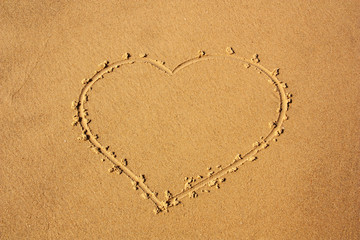 heart depicted on sea sand for background