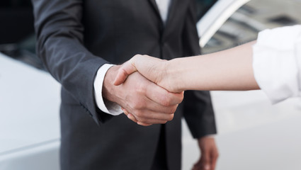 Female salesman shaking hands with customer in dealership