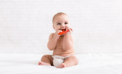 Newborn baby biting red teether in bed