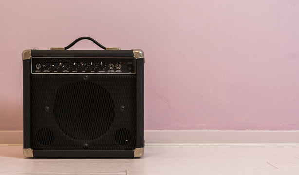 portable electric guitar amplifier isolated in front of a stone wall, music equipment background