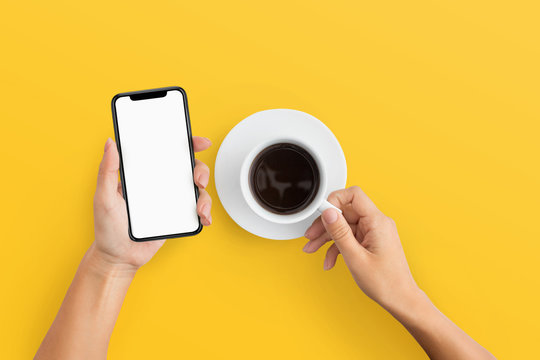 Woman holding mobile phone and coffee cup