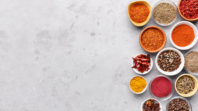 Traditional Indian spices in bowls on grey background