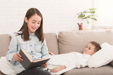 Girl reading book to little sick brother