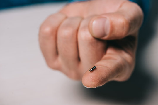 cropped view of man holding  microchip on finger