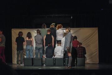 Comédiens sur une scène de théâtre le rôle principal est de profil devant la scène et le reste des comédiens de dos durant une pièce de théâtre moderne