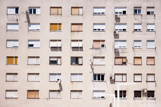 Communist socialist architecture. Architectural detail and pattern of social residential of apartments. Portrait of socialist-era housing district, city building facade. Old apartment windows in city.