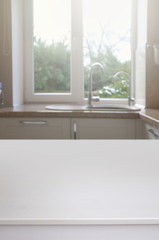 White table against a blurred window in the interior of the kitchen.