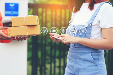 Online shopping, Woman hand holding smartphone and signing receipt of delivery package with delivery man bringing some package at the home, shipping and postal service concept