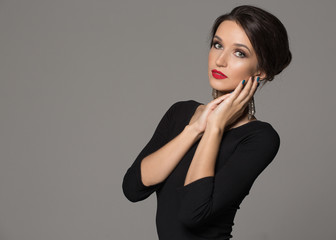 Fashion woman in black dress. Beautiful makeup and hairstyle.