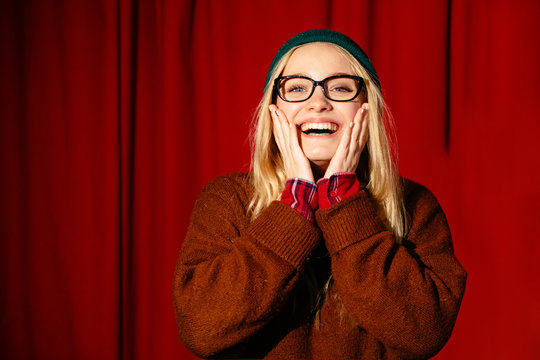 Portrait of young blond hipster woman in eyeglasses performs stand up comedy and joking at a theater over red backstage on background