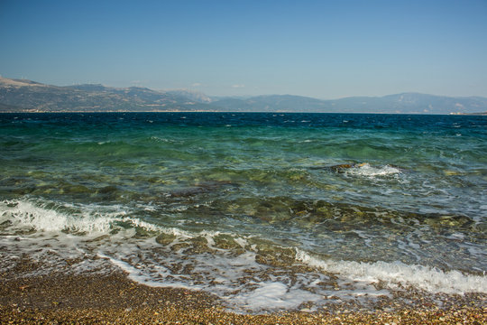 tropic beach sea shoreline waterfront district with waves in vivid blue water surface and mountain landscape horizon background silhouettes