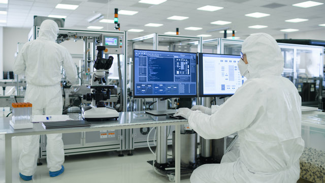 Shot of a Scientists in Sterile Suits Working with Computers, Analyzing Data form Modern Industrial Machinery in the Laboratory. Product Manufacturing Process: Pharmaceutics, Semiconductors.