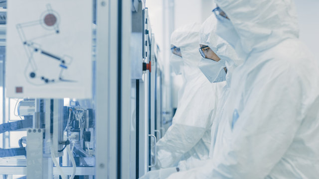 On a Factory Team of Scientists in Sterile Protective Clothing Work on a Modern Industrial 3D Printing Machinery. Pharmaceutical, Biotechnological and Semiconductor Creating / Manufacturing Process.