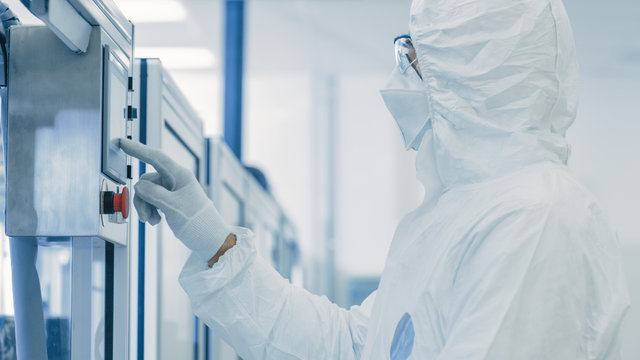 In Manufacturing Facility Scientist Wearing Sterile Protective Coverall and Programs Modern Industrial 3D Printer, High Precision Manufacture of Semiconductors under Process and Presses Start Button.